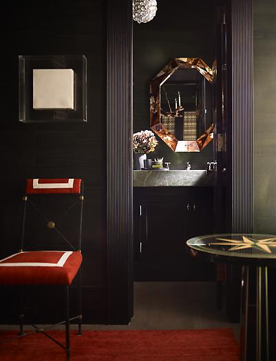 a moody guest toilet with a vanity and a stone sink, a mirror in a metallic geometric frame