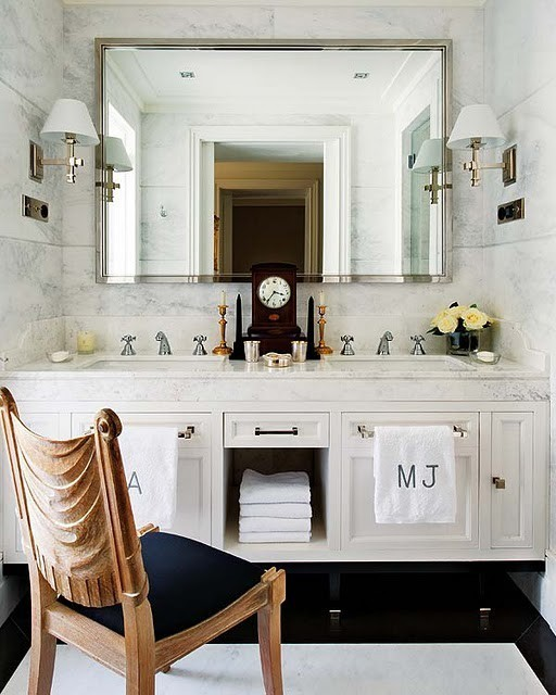 an elegant guest toilet with a large mirror, a neutral mirror with storage and a stone countertop plus a vintage and refined chair