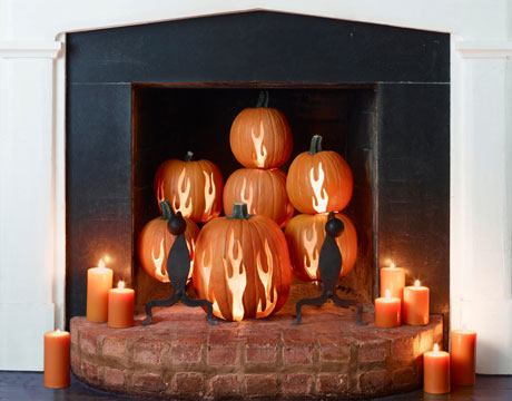 Imitate a real fire with gorgeous stacked carved pumpkins and orange candles.