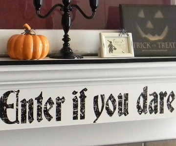 A spooky decal from your local crafts store and apply to a smoothly painted surface. It'd be easy to peel off later.