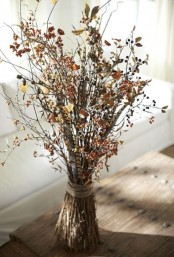 an arrangement of dried leaves and berries is a pretty idea for fall or Thanksgiving decor