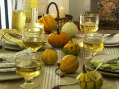 all-natural pumpkins and gourds echo with plates and glasses and give a cozy natural look to the tablescape