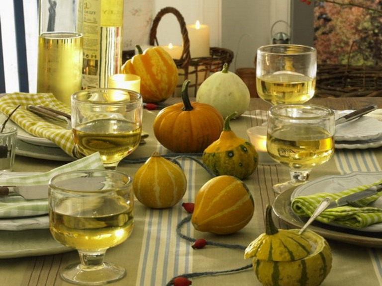 all natural pumpkins and gourds echo with plates and glasses and give a cozy natural look to the tablescape