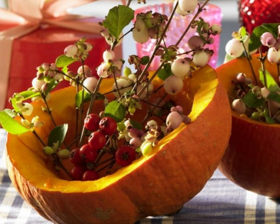 a carved out pumpkin with berries and leaves is a lovely and cool decoration for fall and Thanksgiving