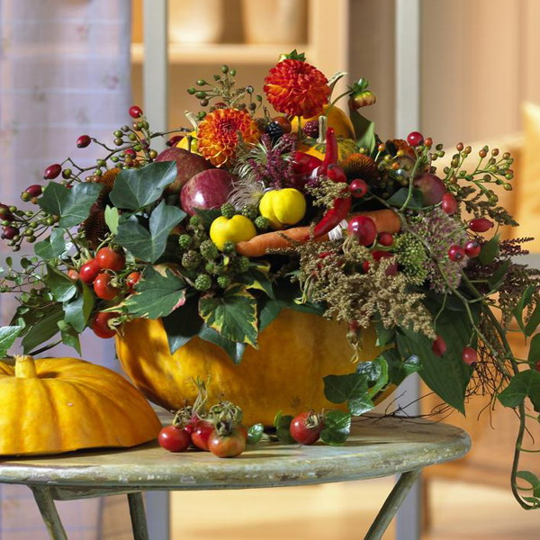 a pumpkin with lots of greenery, bright bold blooms and veggies will be a nice and chic Thanksgiving centerpiece