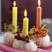 white pumpkins with berries, leaves and colorful candles are pretty decorations for fall or Thanksgiving