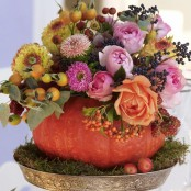 a pumpkin with beautiful blooms, greenery leaves and berries is a stylish rustic and natural Thanksgiving or fall centerpiece