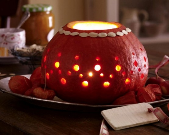 a perforated pumpkin with candles inside is a cool fall or Thanksgiving decoration or a centerpiece to rock
