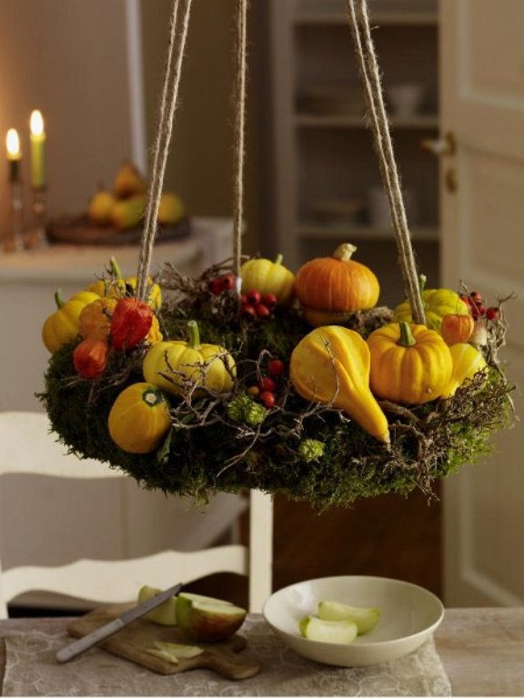 a rustic chandelier of moss, with berries, gourds and dried blooms is a cool decoration you can DIY