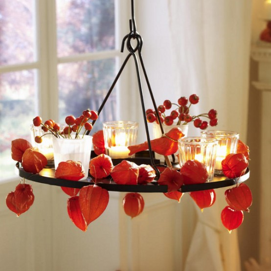 a chandelier with dried blooms, berries and candles is a bold and rustic decoration to rock for fall or Thanksgiving