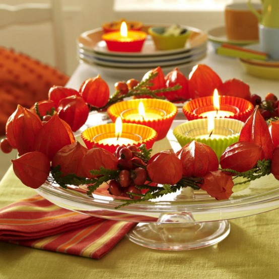 a glass stand with candles, berries and dried blooms is a pretty fall centerpiece of decoration to make