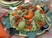 a fall or Thanksgiving centerpiece of leaves, greenery and berries and a bright pepper in the center is easy to make