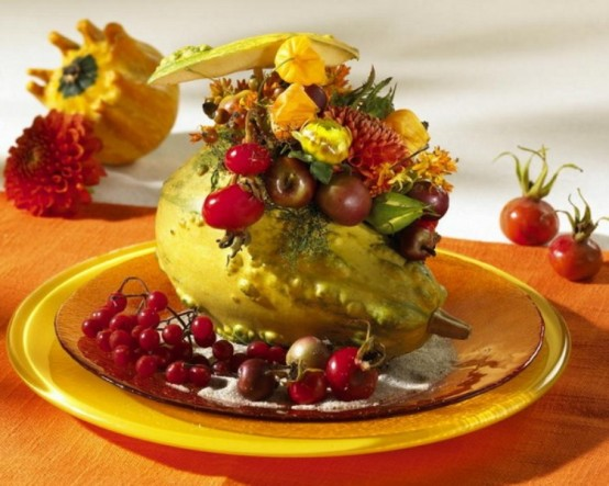 a gourd filled with bright blooms and vegetables and berries on the plate is a very bold and chic Thanksgiving decoration