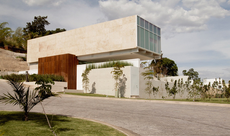 House Composed By Two Rectangular Prisms On A Sloped Site