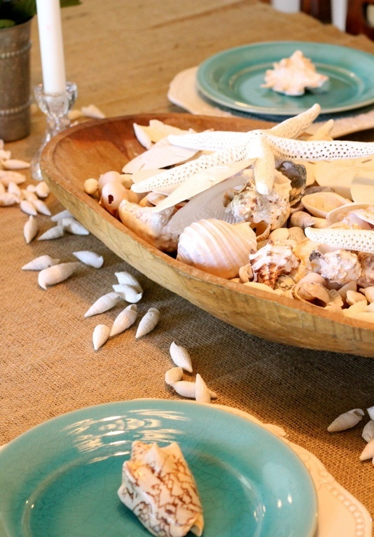 a large wooden bread bowl with seashells and starfish is a perfect and easy centerpiece both for indoors and outdoors