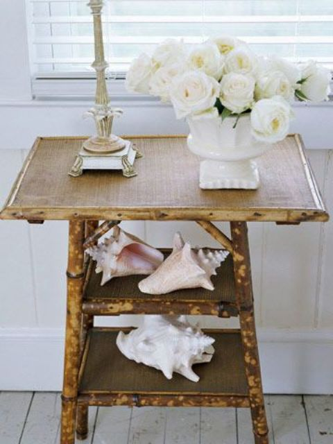 a rustic console table covered with burlap and with large shells and white blooms for beachy decor