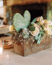 a rusty tin planter with succulents, cacti, moss and hay can be used as a pretty and chic centerpiece with a desert feel