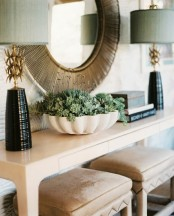 a white bowl with succulents and some dried blooms is a pretty and eye-catchy decoration to rock