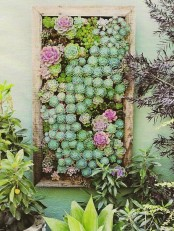 a large vertical planter with succulents and flowers is a veyr bold and chic solution to go for