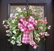 a fresh pink bloom wreath with a pink plaid bow is a bold summer-like decoraiton for your front door