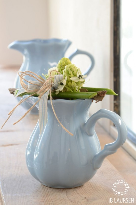 vintage blue teapots and milkpots with greenery and neutral blooms will give a slight vintage or rustic feel to the space