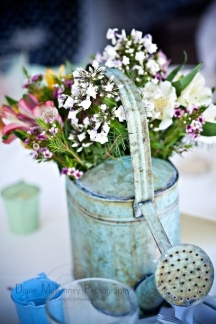 a vintage blue watering can with some wildflowers can be a nice decoration or centerpiece for any occasion