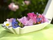 a white bowl with some colorful flower heads is a cool bright centerpiece or decoration for a vintage space