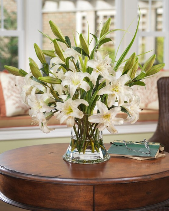 a clear vase with lots of white lilies is an elegant and chic decoration or centerpiece for any party