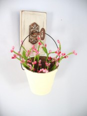 a white bucket with pink blooms hanging on a vintage key is a lovely decoration for both indoors and outdoors