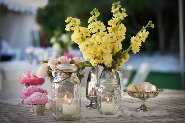 jars and a vintage silver teapot with bright summer blooms and candles for a cool bright summer centerpiece