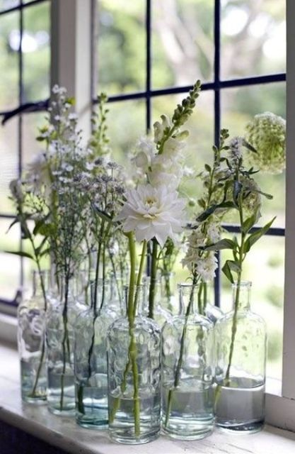 a stack of clear bottles with white blooms will give an ethereal and airy touch to your space, with a boho feel