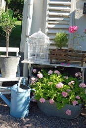 buckets and metal planters with bright pink blooms will give a bold summer yet rustic touch to your outdoor space