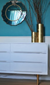 an IKEA Malm dresser hack with tall metal legs and shiny contact paper in between the drawers