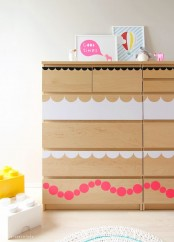 a light-stained IKEA Malm dresser hacked with simple white and pink decals on the drawers