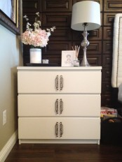 a white IKEA Malm dresser hacked with catchy geometric handles in the center