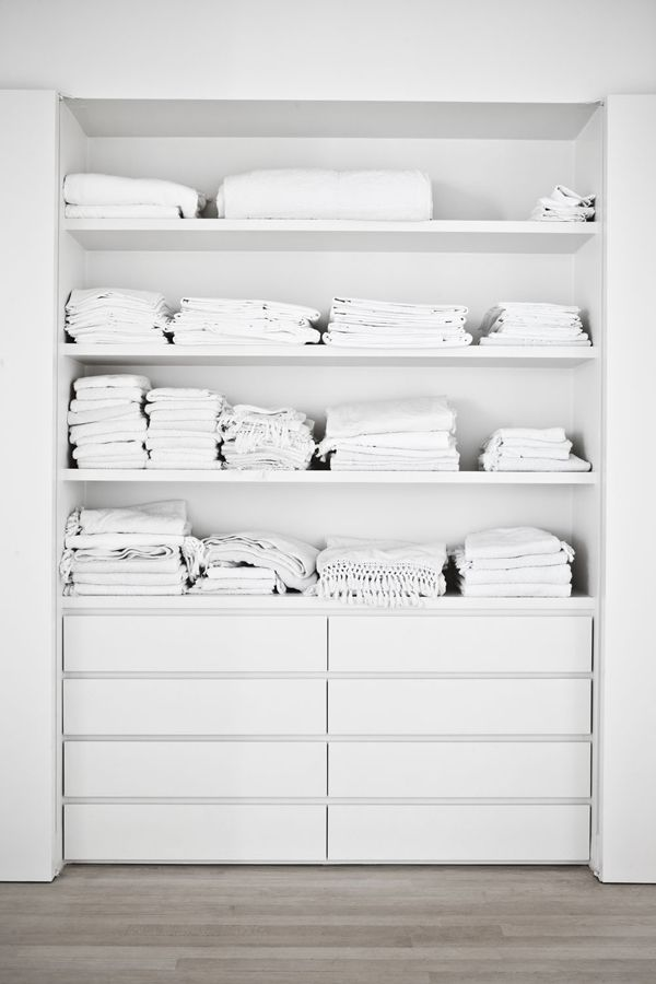 a built in closet with open shelving and IKEA Malm dressers for smaller items is a simple and cool idea