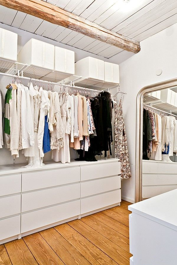 a welcoming and airy closet with open shelving and holders plus some Malm dressers for storage