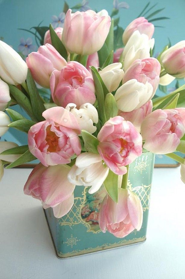 a light blue vintage tea can with pink and white tulips is a pretty vintage inspired centerpiece