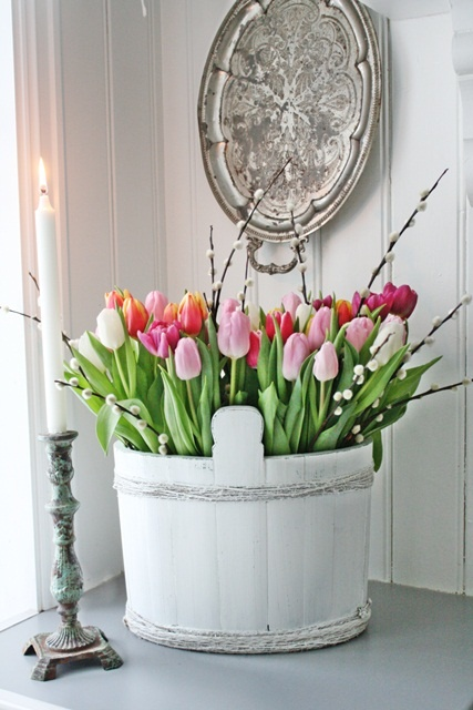a white wooden bucket with colorful and white tulips plus willow is a beautiful spring decoration or centerpiece