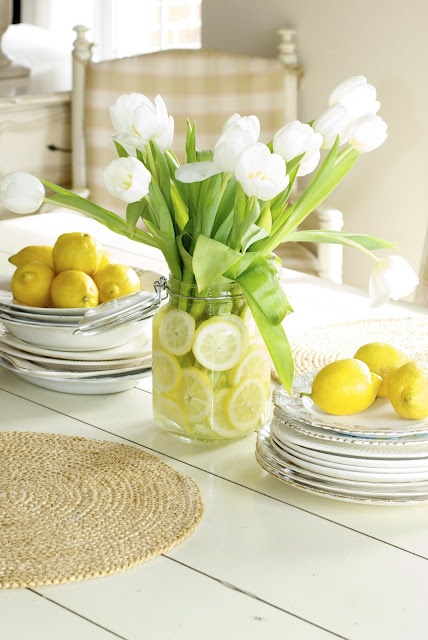 a white jar with white tulips and citrus slices inside is a simple and cool spring centerpiece for every space