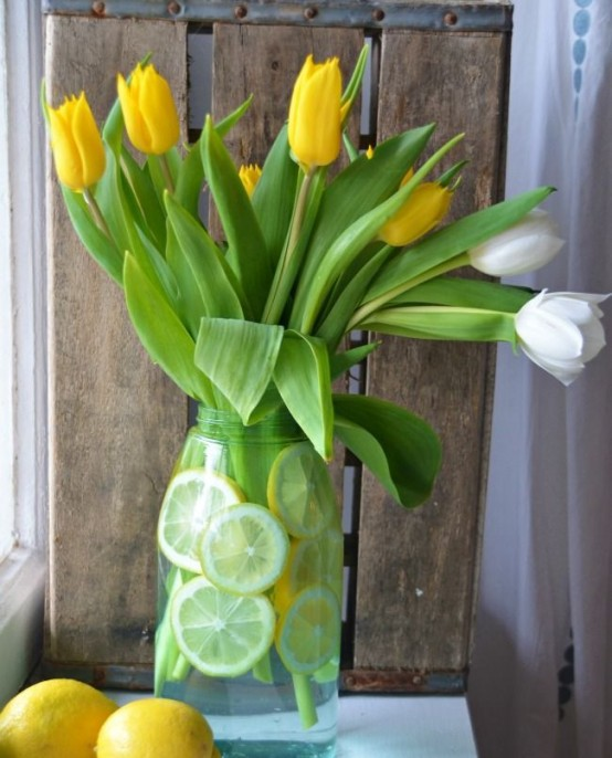 a clear vase with citrus slices and white and yellow tulips is a bright and cheerful spring centerpiece