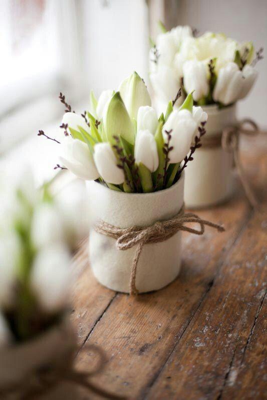 white vases with white tulips, blooms and twine accenting the vases to make them spring-like