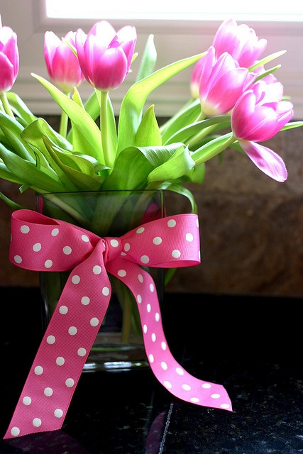 a clear vase with bright pink tulips and a hot pink polka dot bow on the vase for adding a cheerful touch to the space