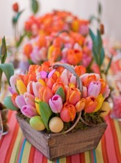 a wooden box with moss, colorful tulips and fake eggs is a nice Easter decoration with a bright look