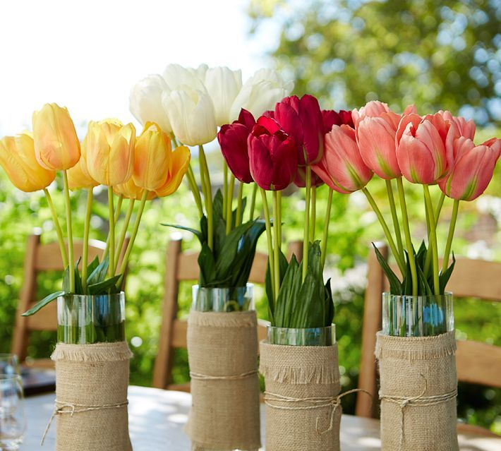 clear glass vases wrapped with burlap and with bright spring tulips are nice decorations, centerpieces for spring