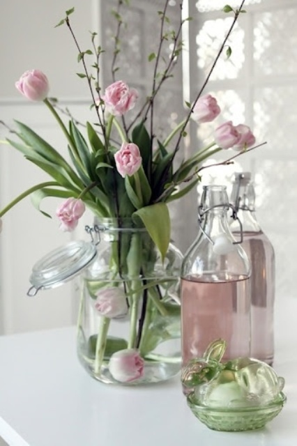 a large clear jar with pink tulips is a cool spring or Easter decoration in a soft spring like color