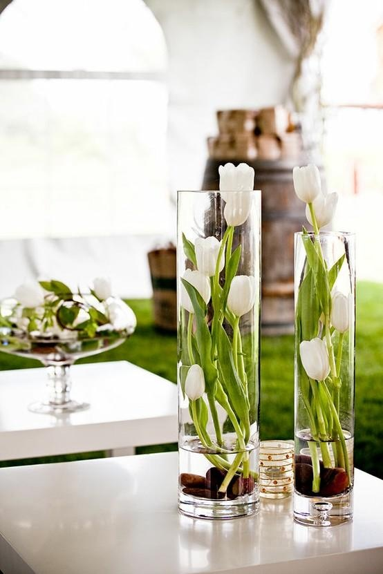 tall clear vases with pebbles and white tulips make up cool spring centerpieces for any celebrations, from parties to weddings