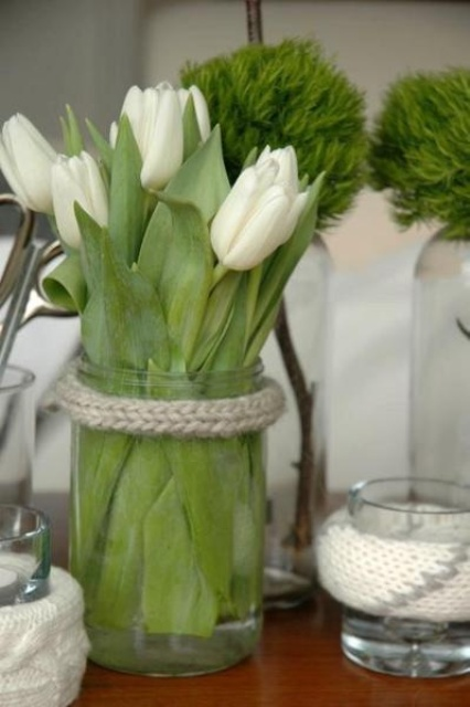 a clear glass jar with white tulips and rope wrapping the jar is a simple rustic decoration or centerpiece