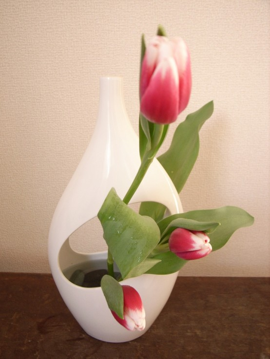 a white cutout back with red to white tulips is a bold ikebana-inspried arrangement for spring decor