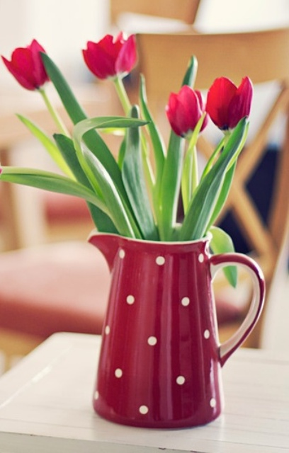 a red polka dot jg with red tulips is a simple and casual spring or Easter decoration to rock, it's a bit retro